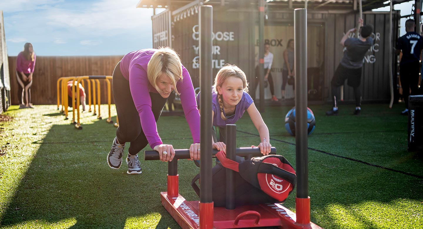 Image of a woman and a younger girl pushing a weighted sled during a battlebox class