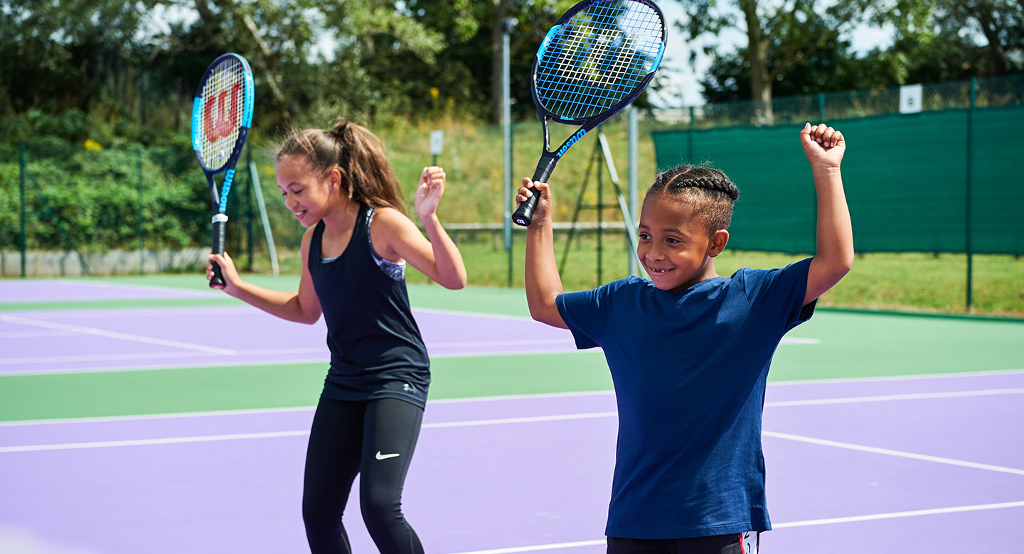 Kids enjoying tennis on an outdoor court.