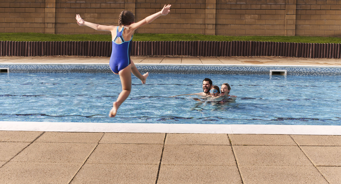 Image of young girl jumping into a swimming pool with family