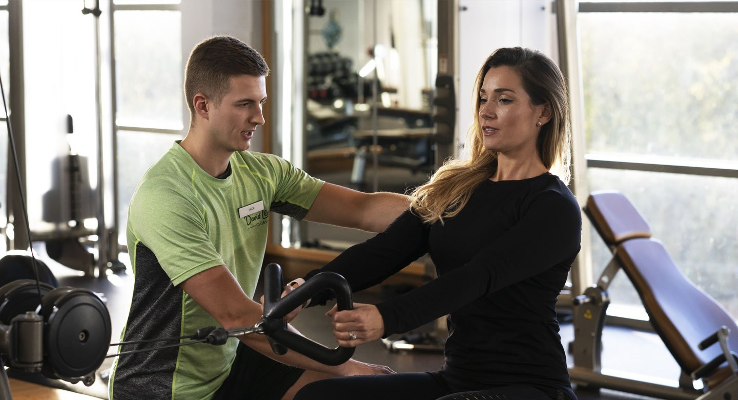 Image of male PT working with a female client on a low row machine