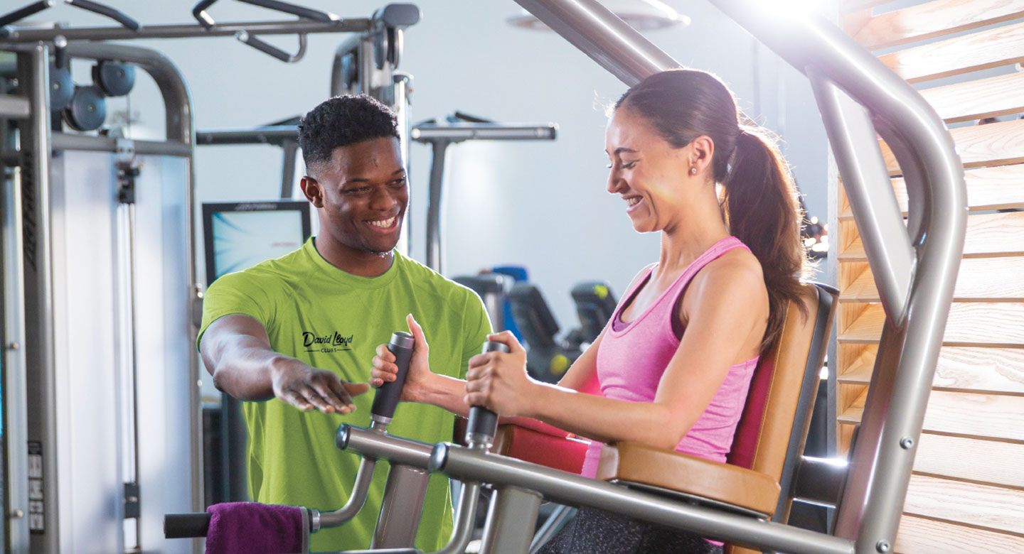 Woman using gym equipment with personal trainer.