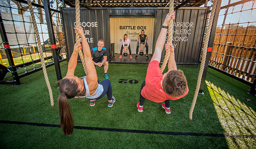 Image of a man and a woman swinging and climbing up ropes during a Battlebox session