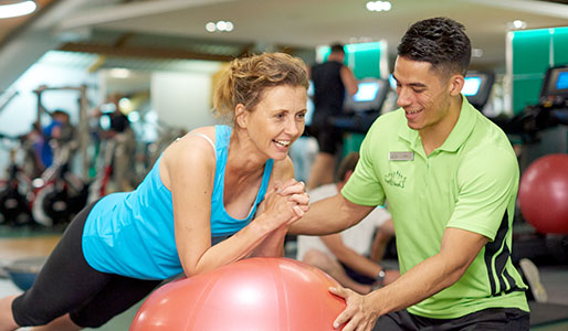 Woman using exercise ball, assisted by a personal trainer.