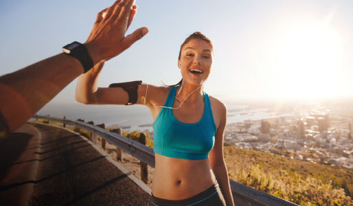 Woman high-fiving having just completed an outdoor run.