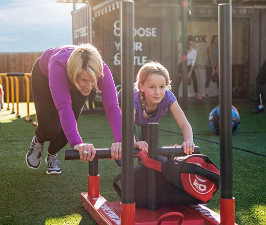 Image of young girl and mother pushing a sled during Battlebox class