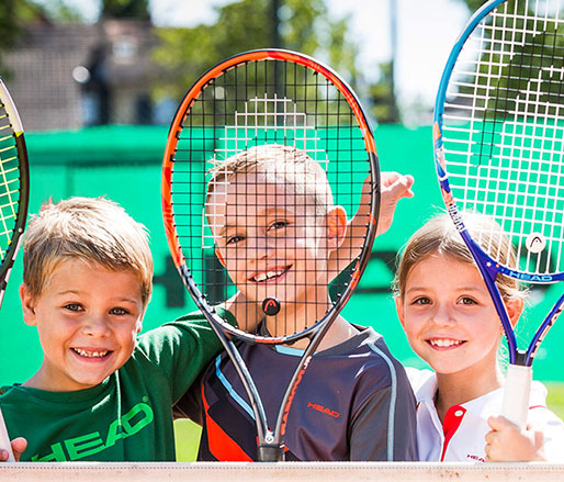 Image of 3 children holding up tennis racquets over their faces