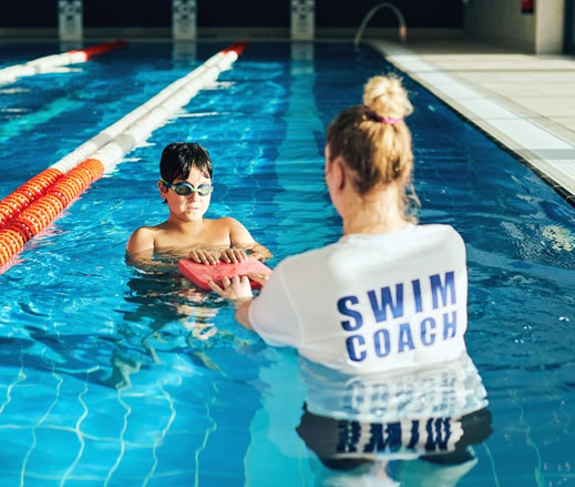 Image of child having a swimming lesson with coach