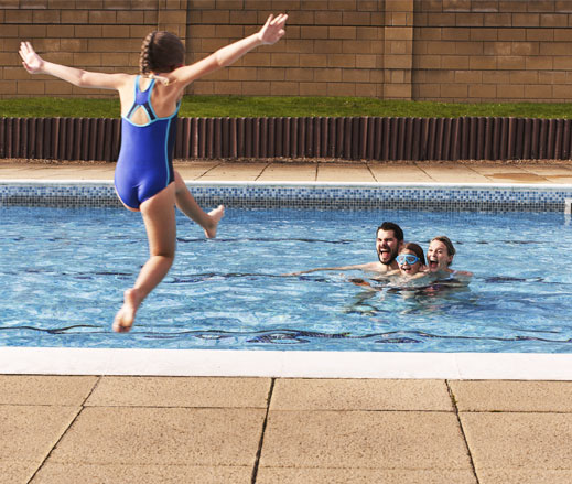 Image of a young girl jumping into pool with family