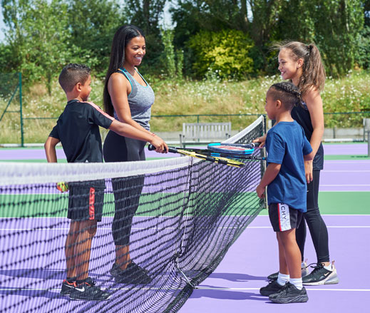 Image of family preparing to enjoy a game of tennis on outdoor tennis court