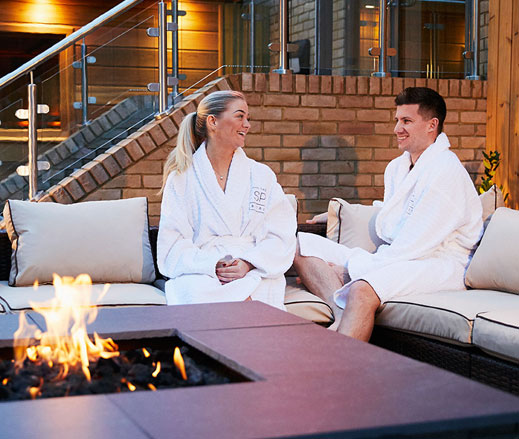 Image of man and woman enjoying time relaxing in the spa garden at David Lloyd Royal Berkshire