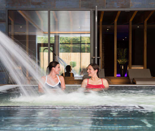 Image of two ladies relaxing in the hydro pool at David Lloyd Chigwell