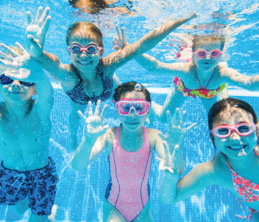 Image of 5 children swimming in a pool.
