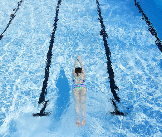 Image of a lady swimming in an outdoor pool