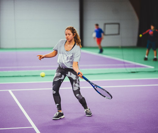 Image of teenage girl hitting a forehand on an indoor tennis court at David Lloyd