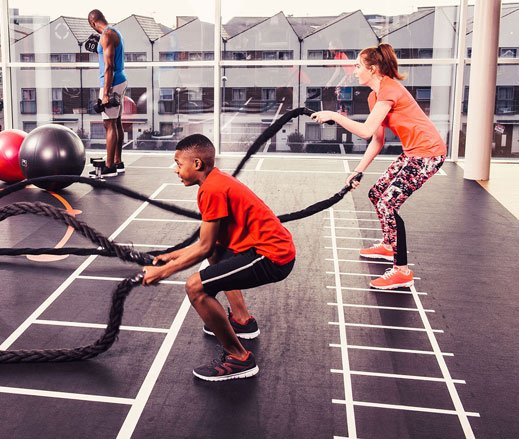 Image of teenagers using the battle ropes in the gym