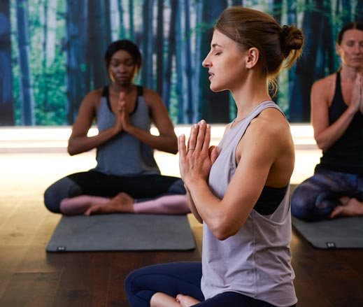 Image of three women taking part in a yoga class