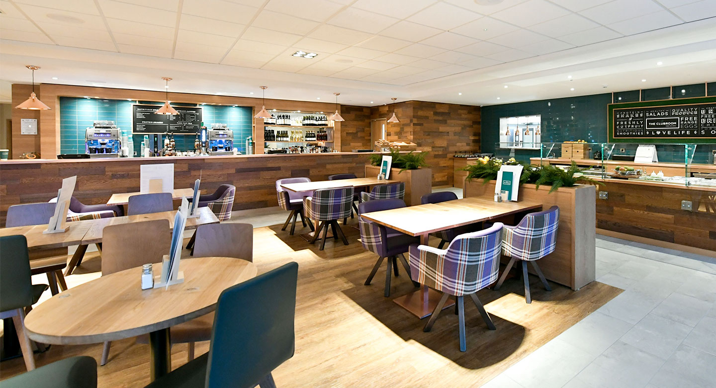 Image of the Clubroom at David Lloyd Acton Park, with tables and chairs and a bar