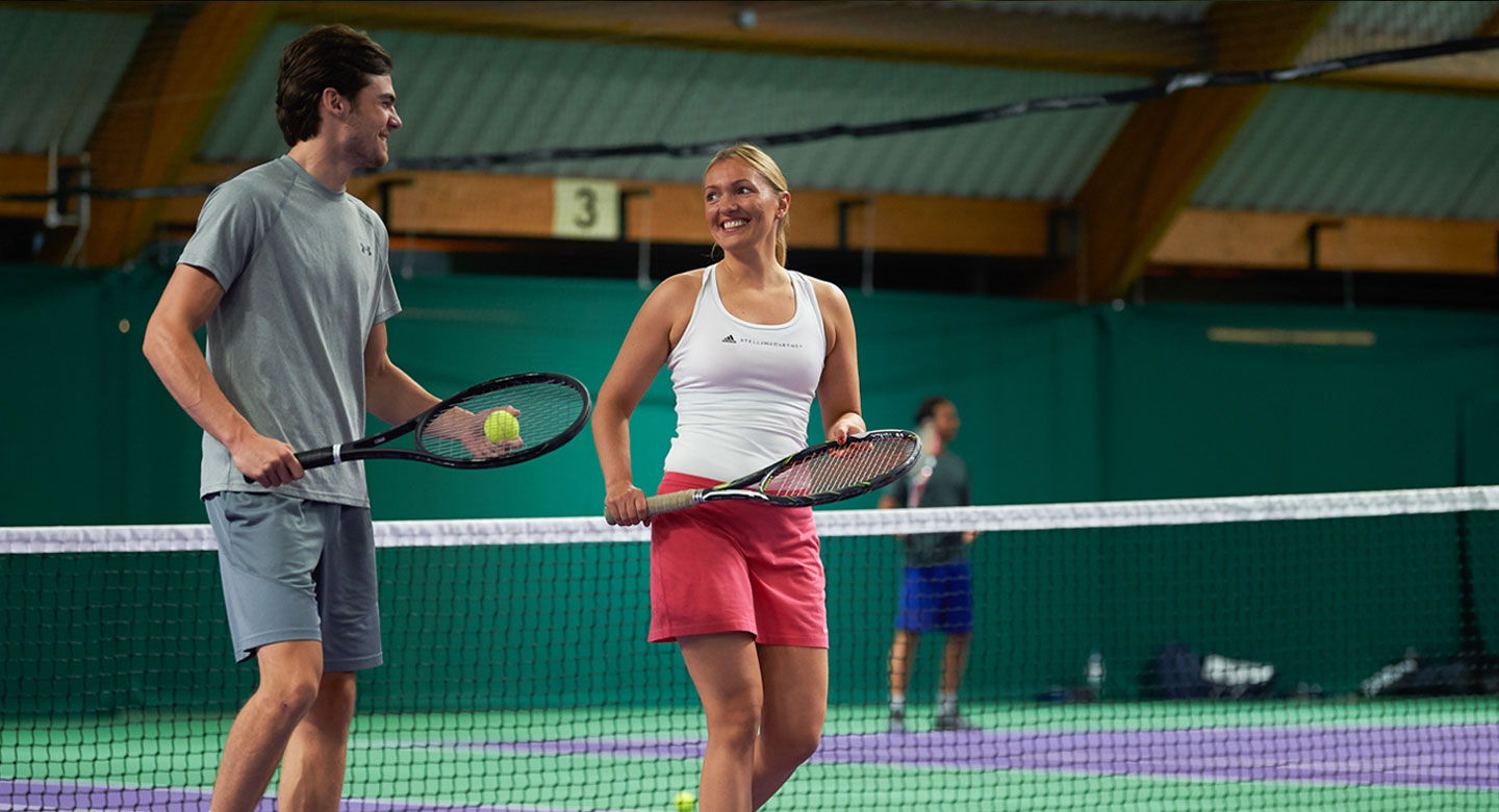 Image of a man and a woman playing tennis on the indoor court at David Lloyd Chigwell