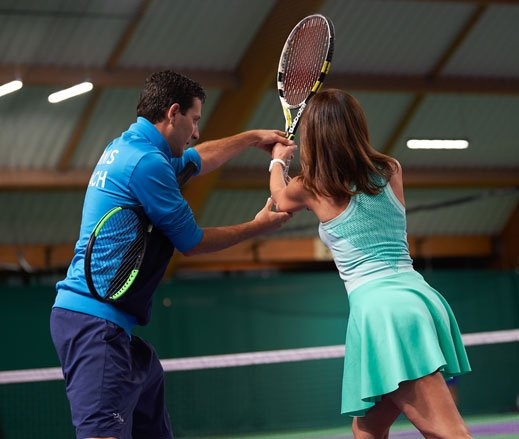 Image of a tennis coach working with a female tennis player