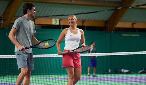 Image of a man and woman playing tennis on the courts at David Lloyd Chigwell