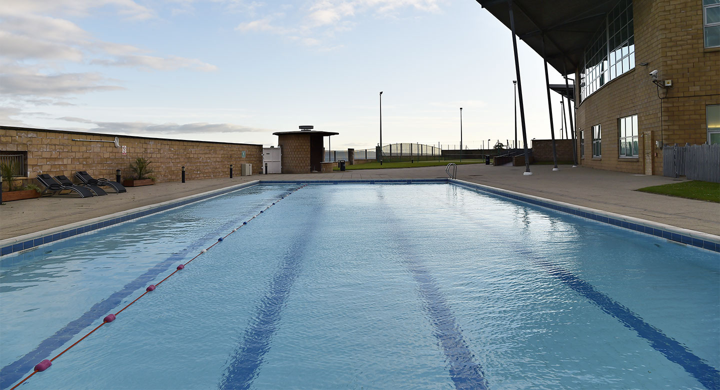 A regtantular outdoor pool with one swimming lane and an open space.