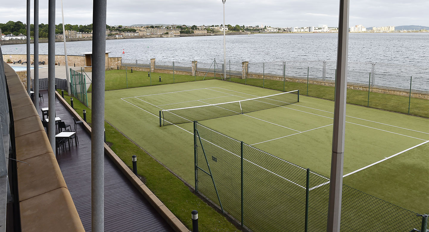 An Outdoor tennis court with the water running along side.
