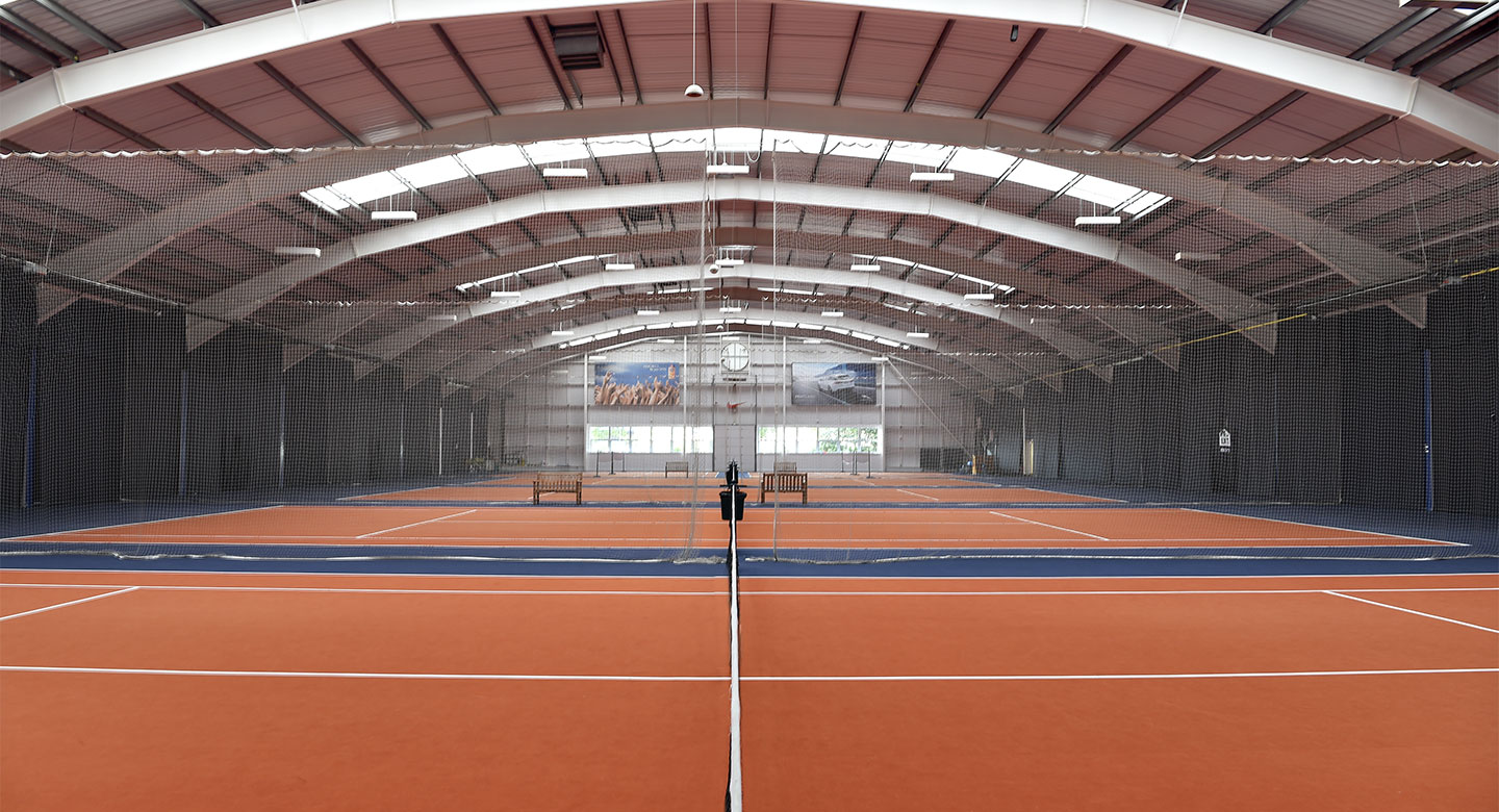 A large indoor space separated into tennis courts.