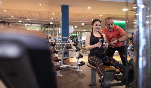 Image of a lady using the low row machine with a PT