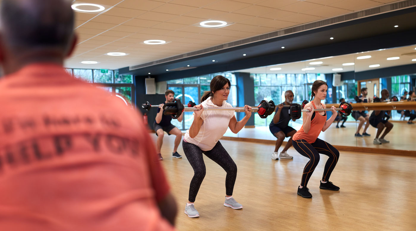 Image of people taking part in a bodypump class with the instructor in the foreground