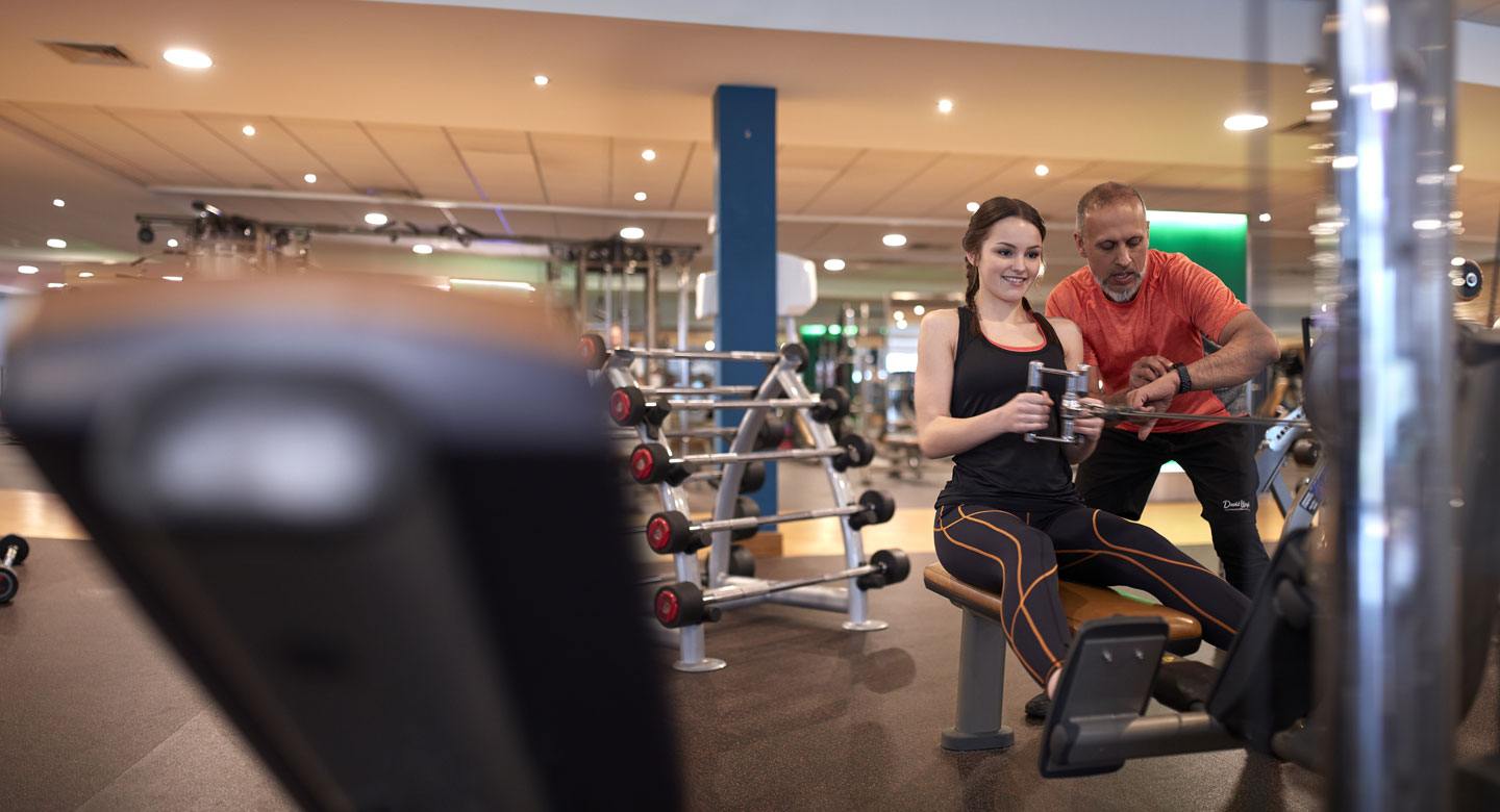 Image of a girl with a trainer using the low row machine at a David Lloyd gym