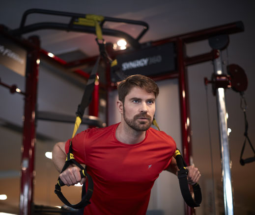 Image of man using the TRX strap on the synrgy unit in the gym