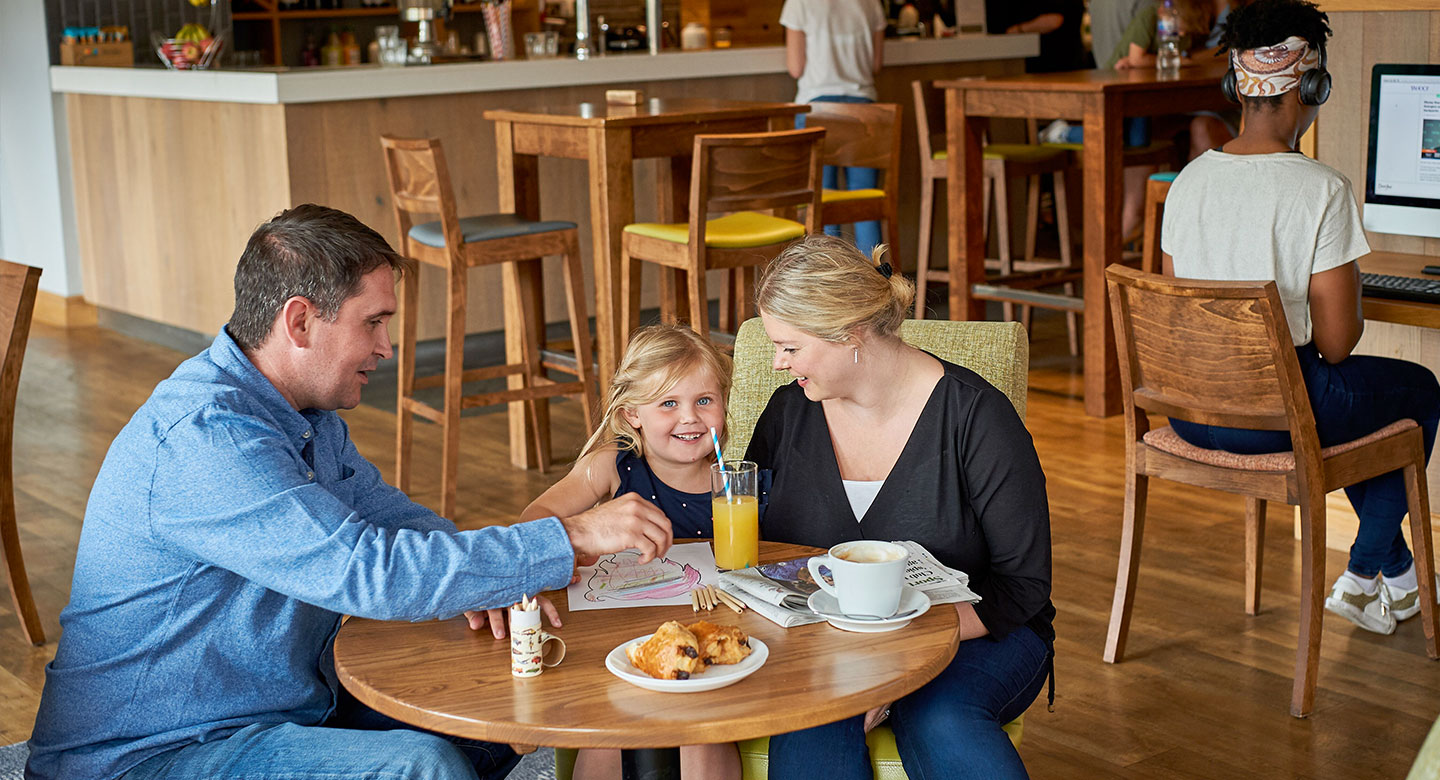 Image of a family enjoying a meal in the clubroom at David Lloyd Purley