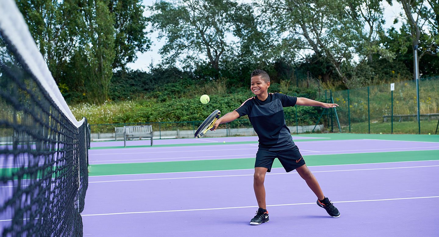 Image of a young boy playing a backhand volley on the tennis court at David Lloyd Purley