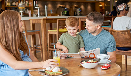 Image of a family reading a magazine in the clubroom at David Lloyd Purley