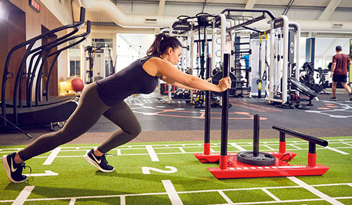 Image of a woman pushing a weighted sled in the gym at David Lloyd