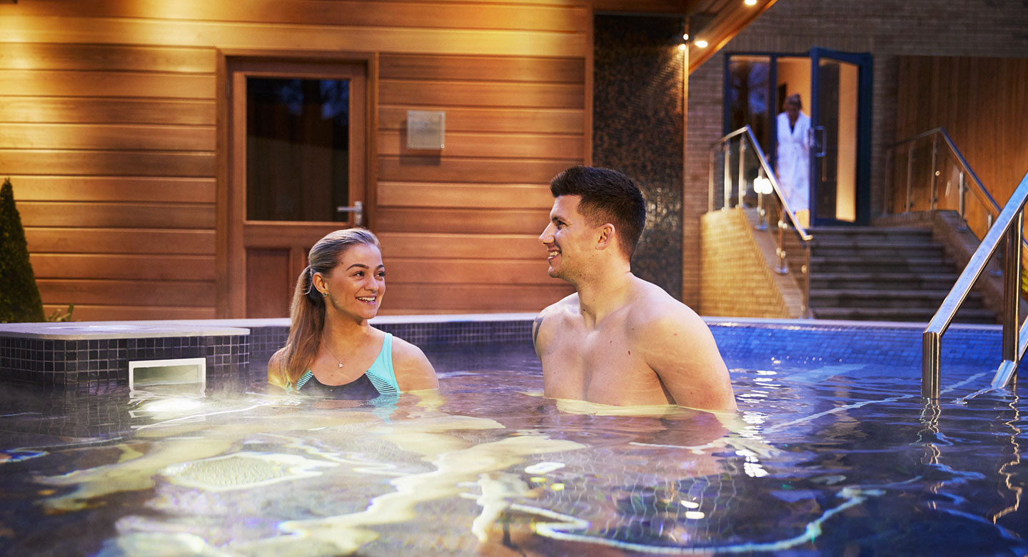 Image of a man and a woman enjoying the outdoor hydro pool at David Lloyd