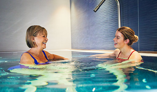 Mother and daughter laughing and smiling in the hydropool at David Lloyd Royal Berkshire
