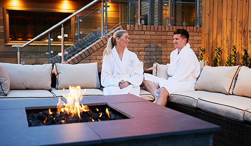 Lady and man sat on the sofa in the outdoor spa garden at David Lloyd Royal Berkshire