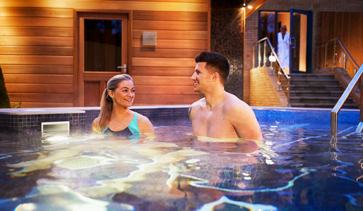 Image of man and woman relaxing in an outdoor hydro pool at David Lloyd