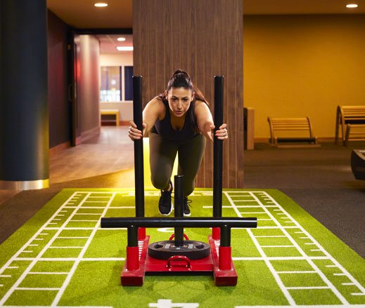 Image of a woman in the gym pushing a weighted sled