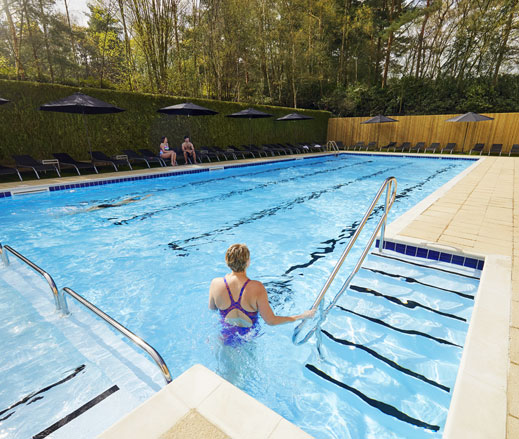 Image of a lady entering the outdoor pool at David Lloyd Royal Berkshire