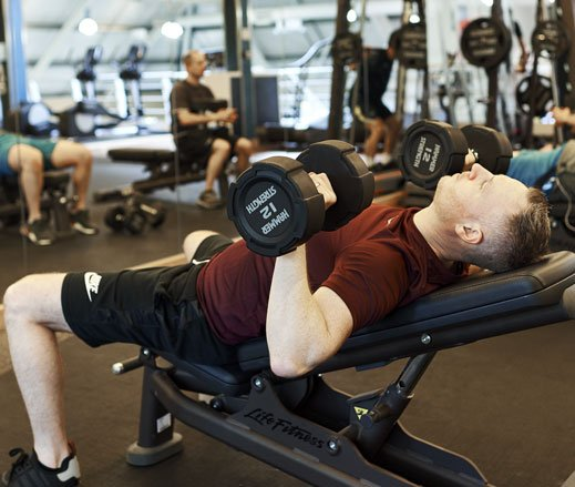Image of a man doing the dumbbell press exercise in the gym