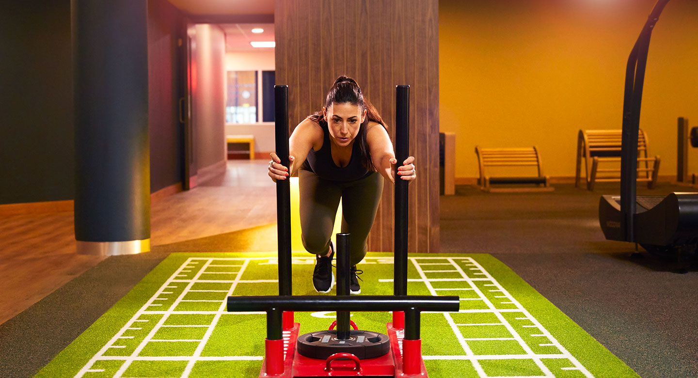 Image of lady pushing weighted sled in gym