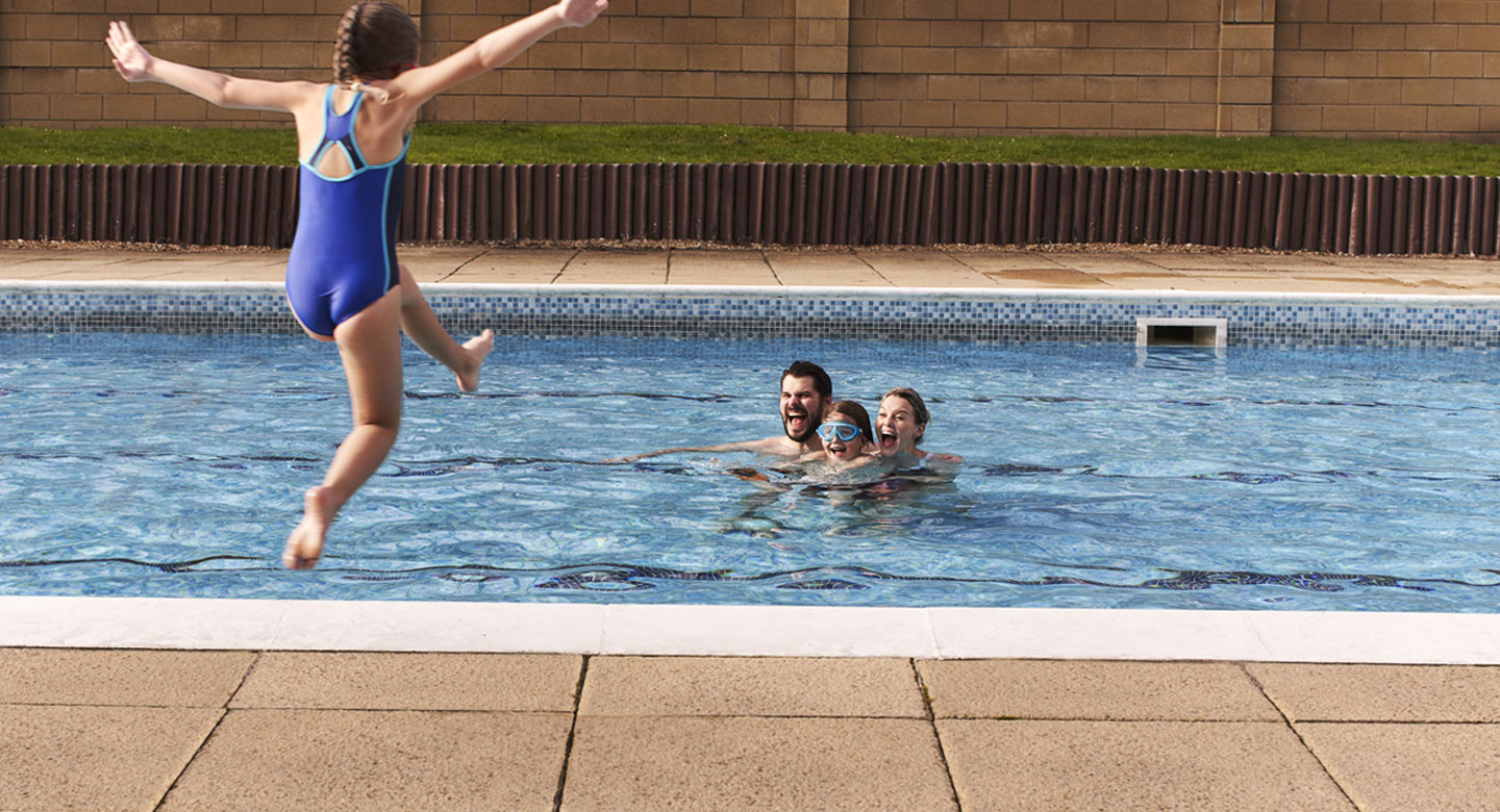 Image of a girl jumping into an outdoor pool with family