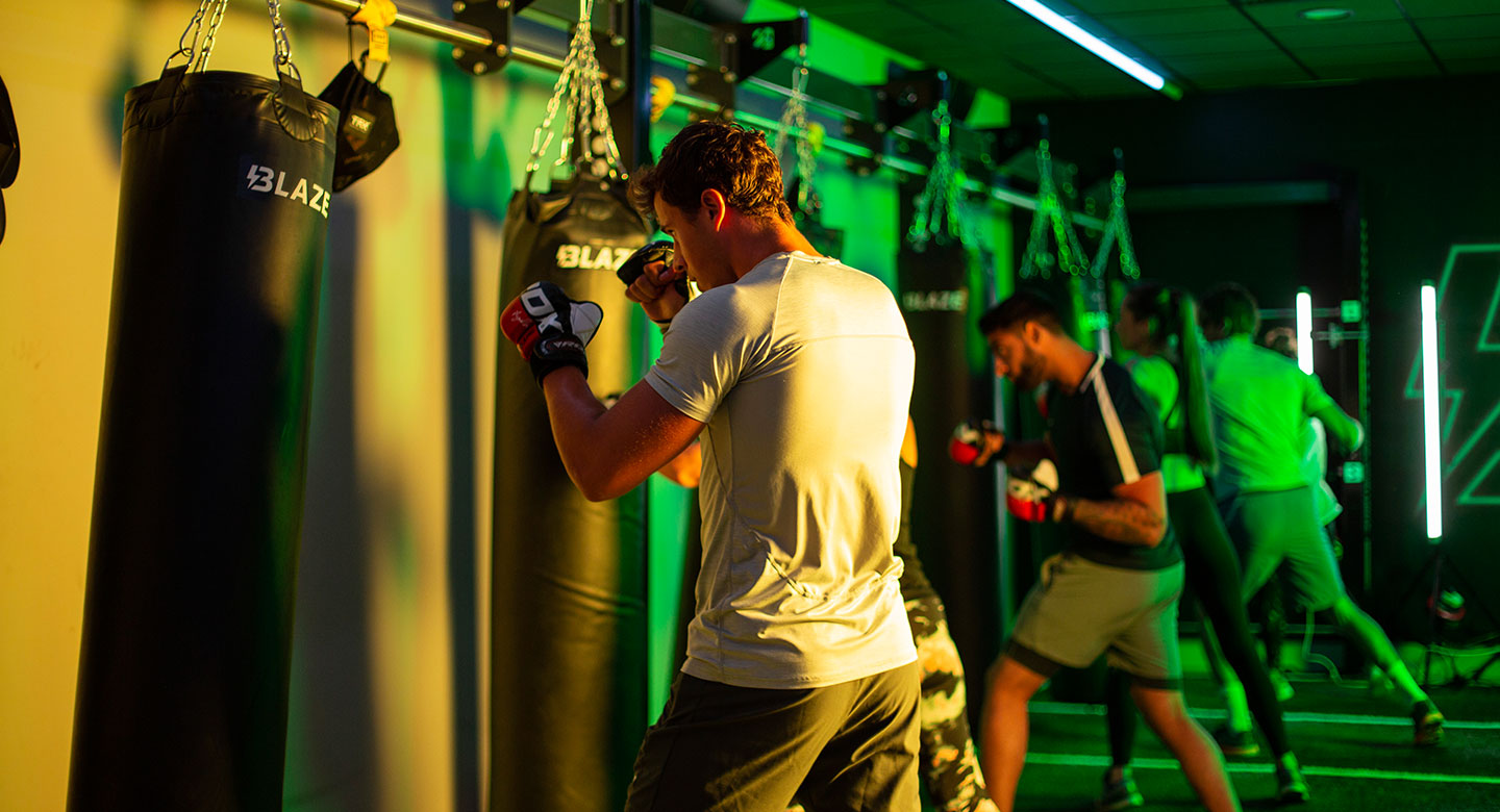 Image of two men punching a punchbag during a Blaze class