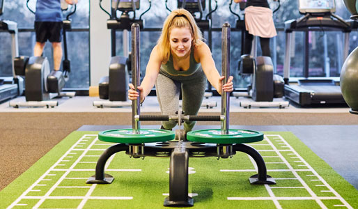 Image of female pushing a sled in the gym at David Lloyd