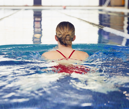 Image of lady swimming in indoor pool at David Lloyd