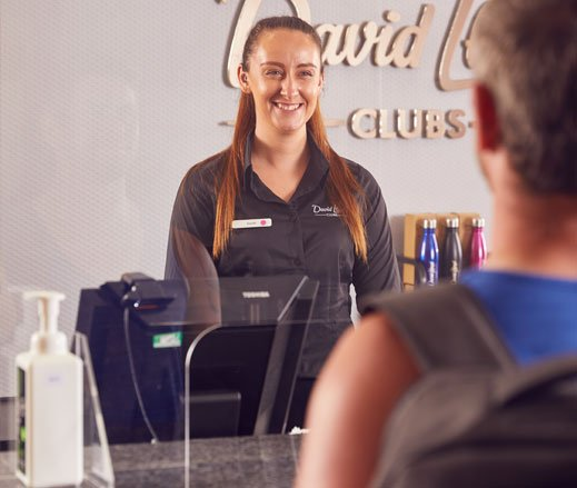 Image of receptionist behind plastic screen at David Lloyd