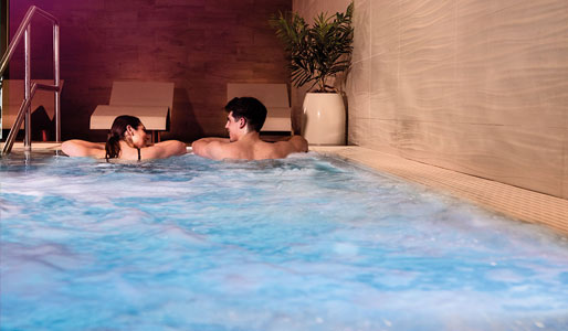 Image of man and woman relaxing in the hydro pool at a David Lloyd spa