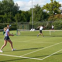 A doubles match on an outdoor tennis court.